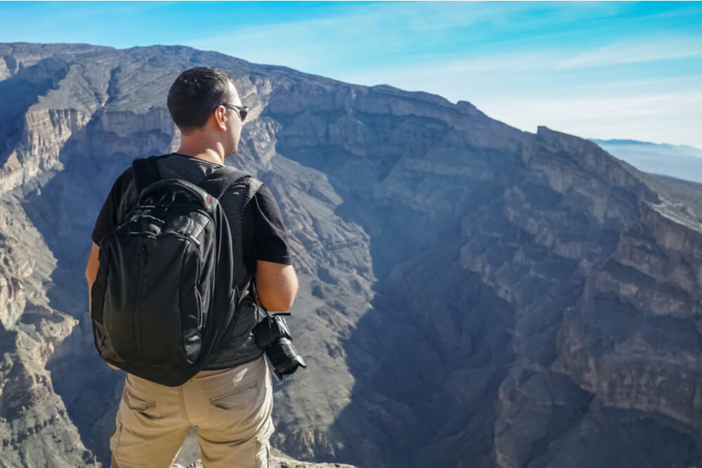 a male tourist with backpack and camera enjoying view of Wadi Ghu in Oman