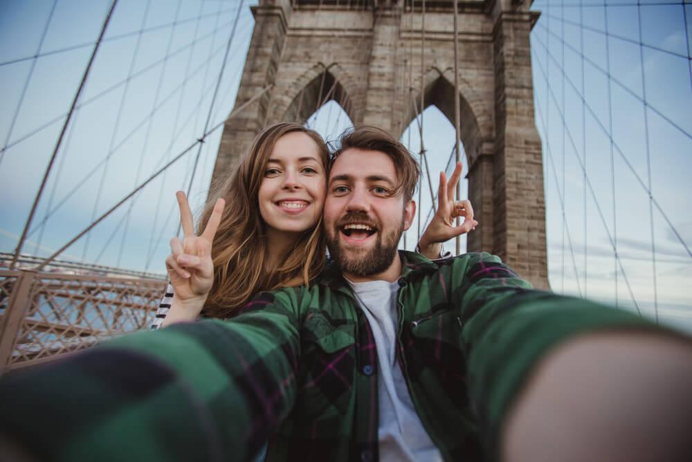 Couple with personal liability insurance taking selfie on Brooklyn bridge