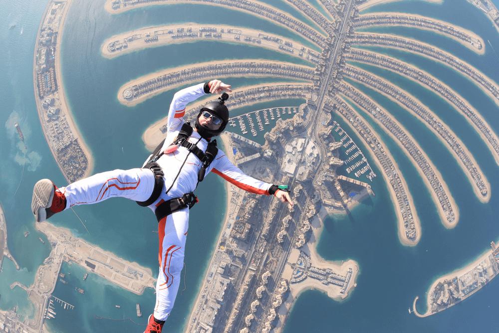 a man skydiving over man made Dubai Palm Islands