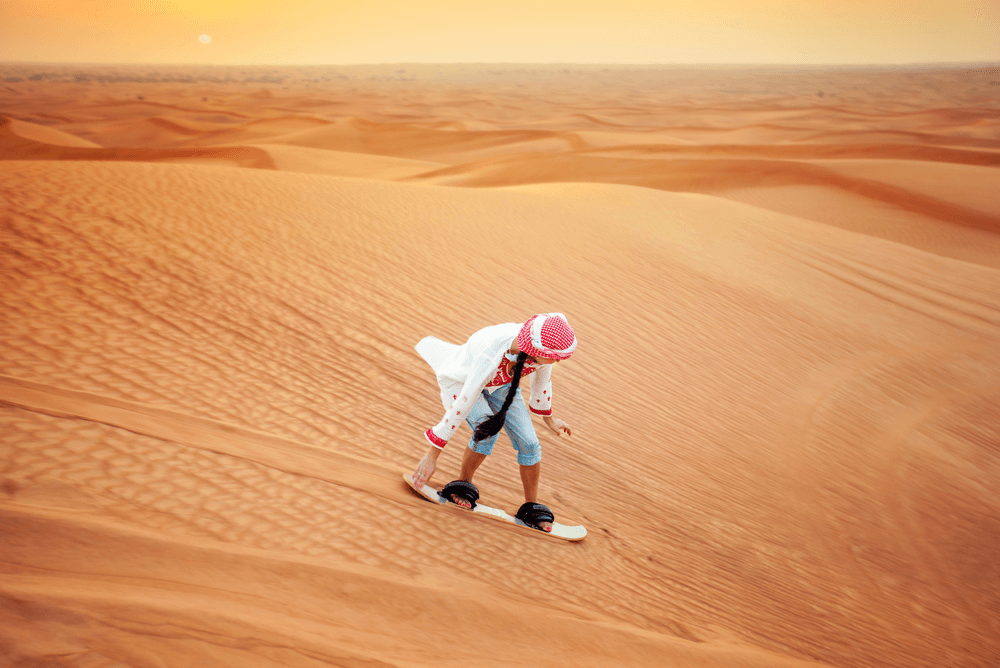 a tourist sand boarding in the desert in the UAE