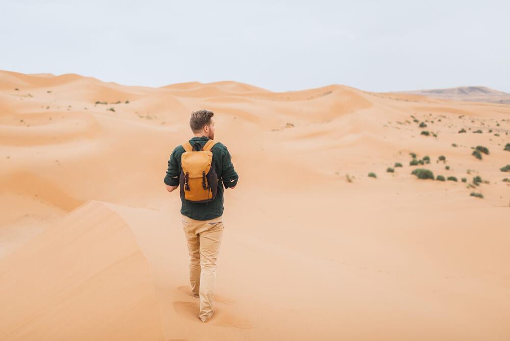 a man walking through the sand dunes of the Sahara
