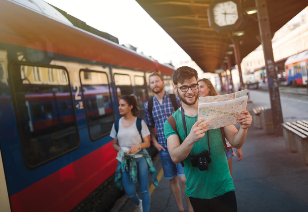 friends on working holiday with travel insurance at train station