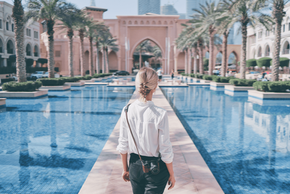 a blonde woman in Dubai facing a walkway between pools