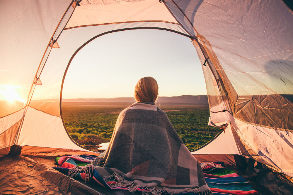 a woman sitting in her tent while camping in South Africa