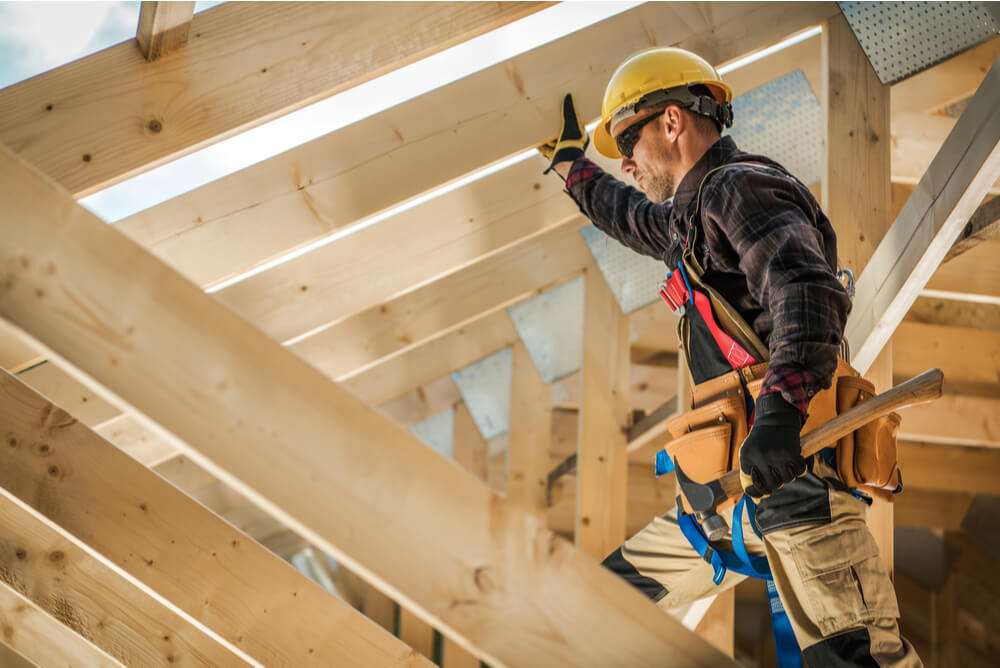 a construction worker building a wooden house frame