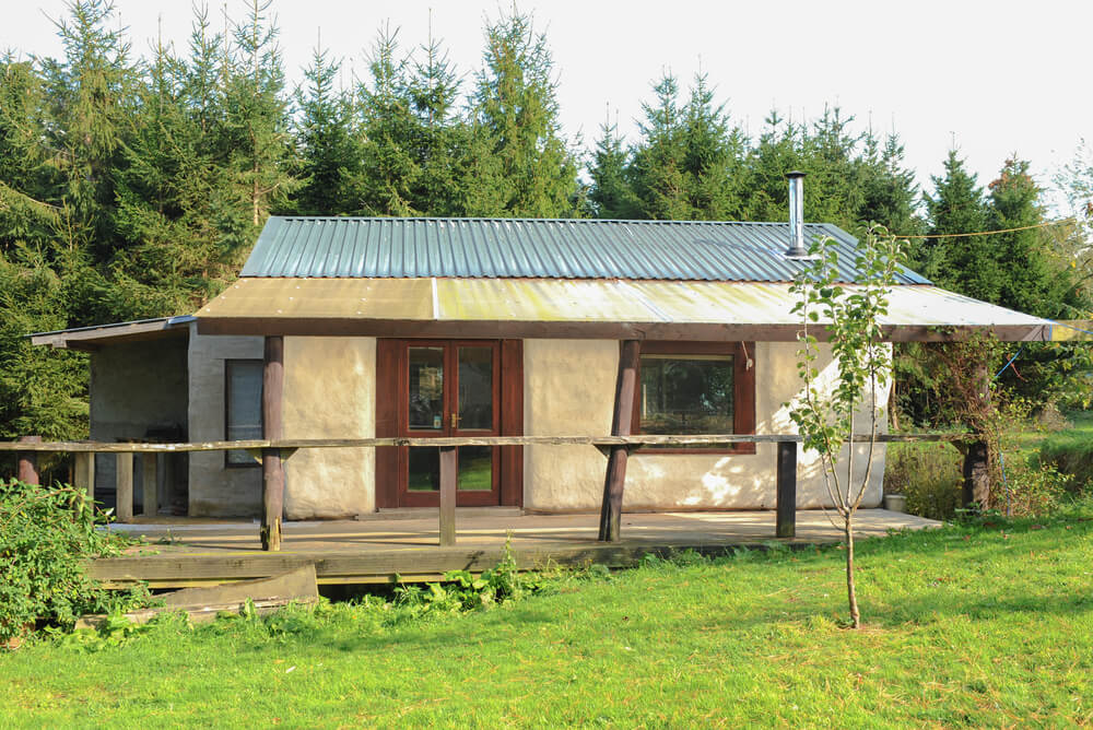 a straw bale house with corrugated roof and wooden patio