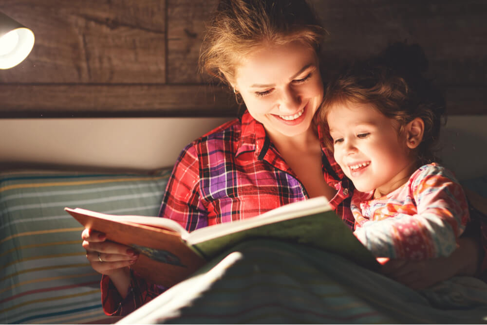 a mother reading her daughter a story by lamplight