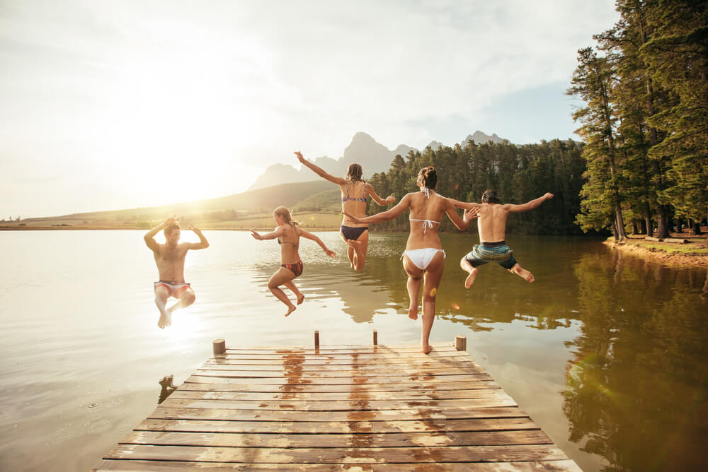 backpackers jumping into a lake