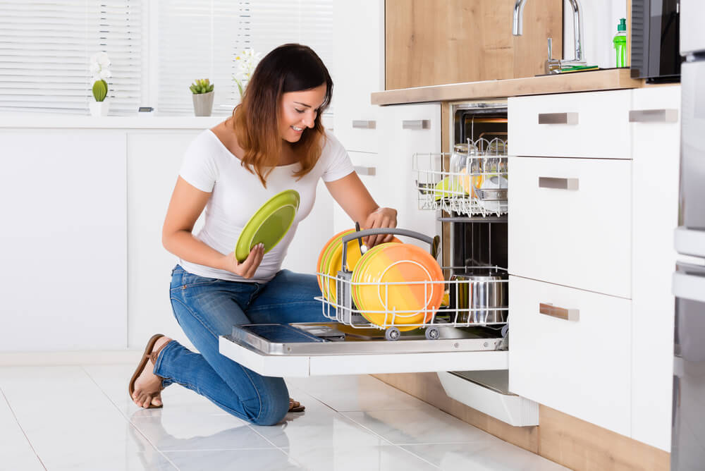 woman using the dishwasher after checking its power consumption