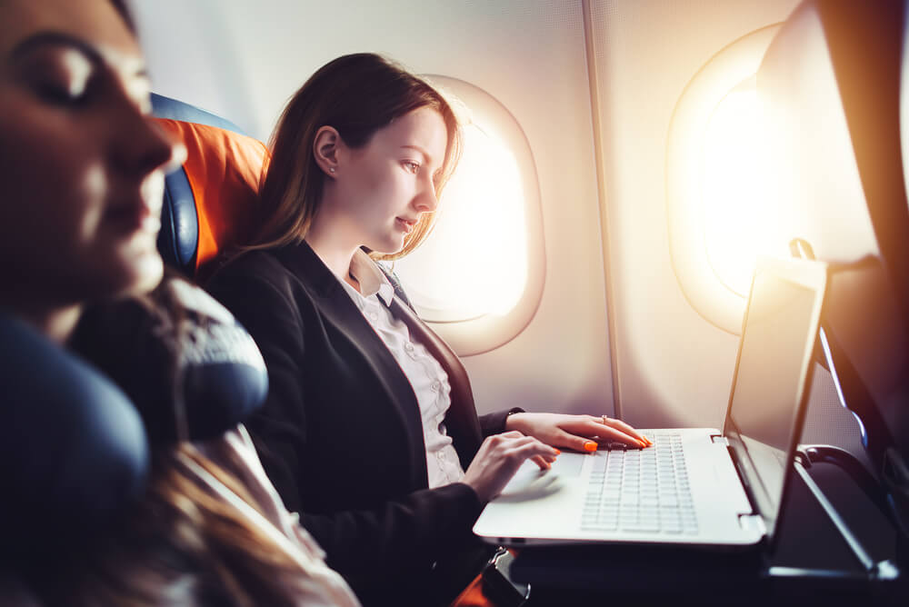 businesswoman working on a laptop seated in a plane