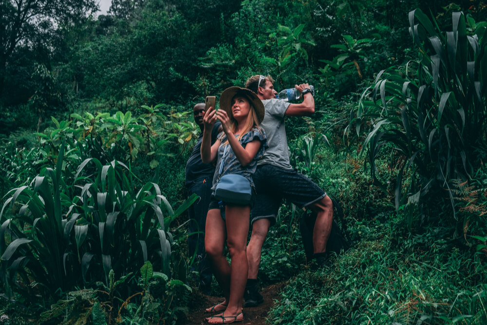 two tourists taking photos in a jungle with travel insurance covering medical evacuation repatriation