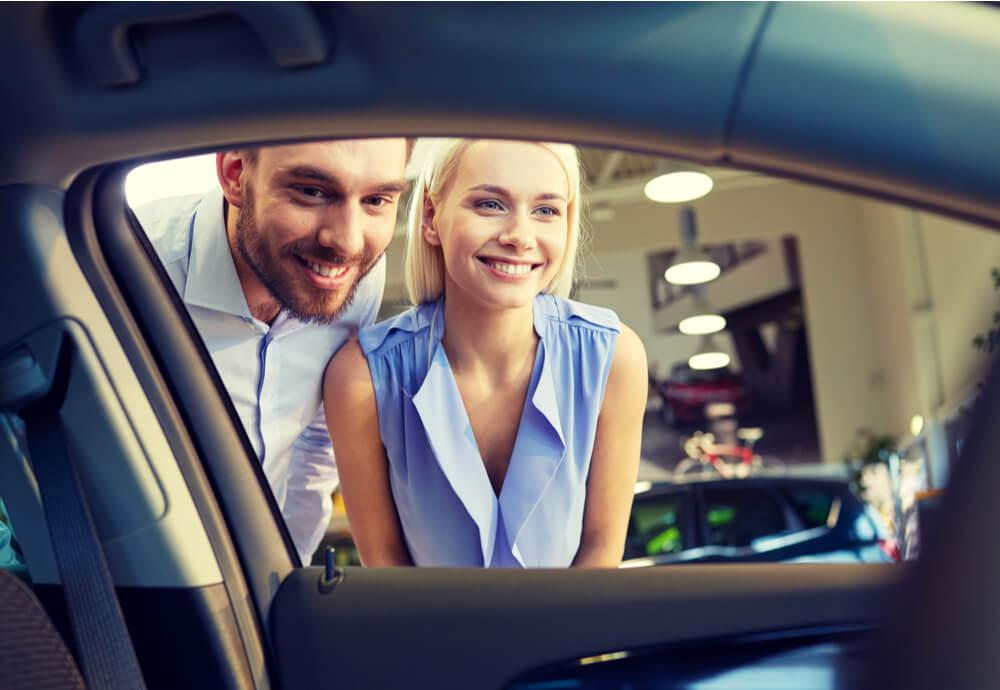 a couple looking through a car window into the interior of a car