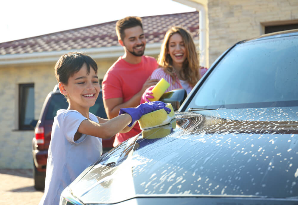 a family washing their car in the driveway