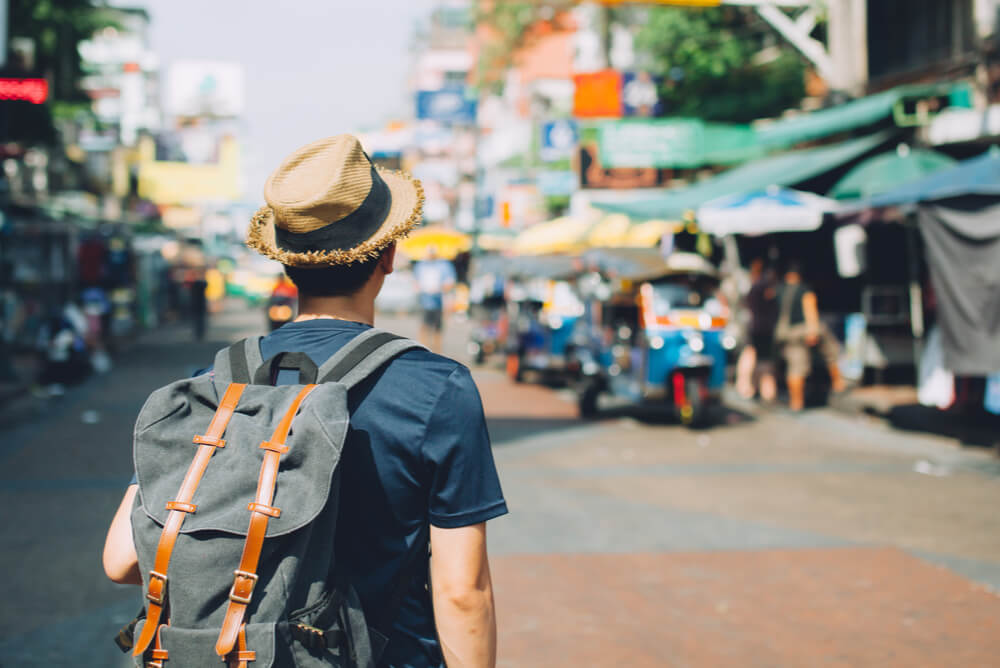 man with backpack walks through a market in Thailand
