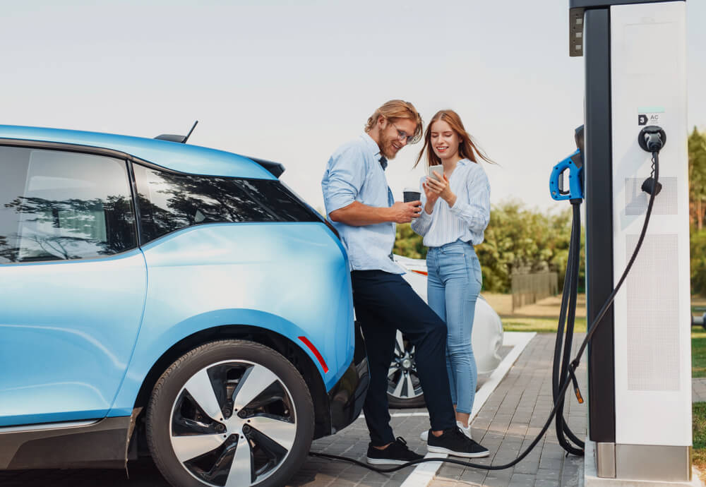 a couple standing next to their blue EV while it recharges