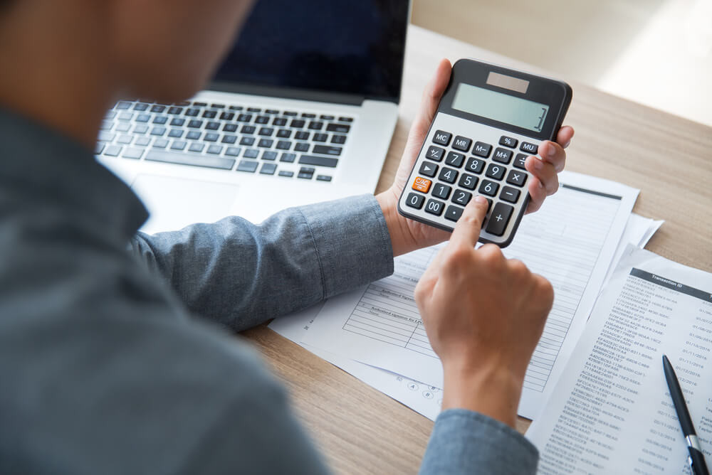 Man using a calculator with paperwork and a laptop