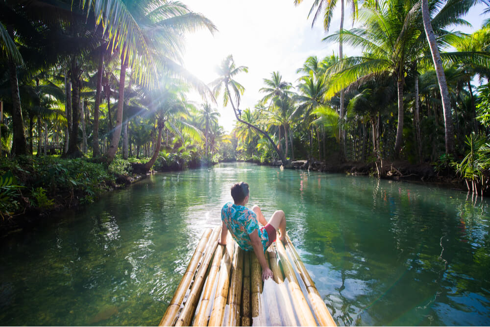 tourist on a bamboo raft with a one way travel insurance policy