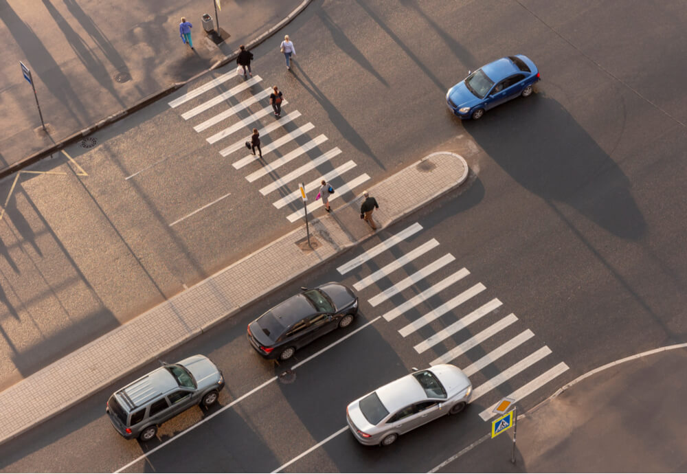 an aerial view of a pedestrian crossing with people walking across it and cars on the road