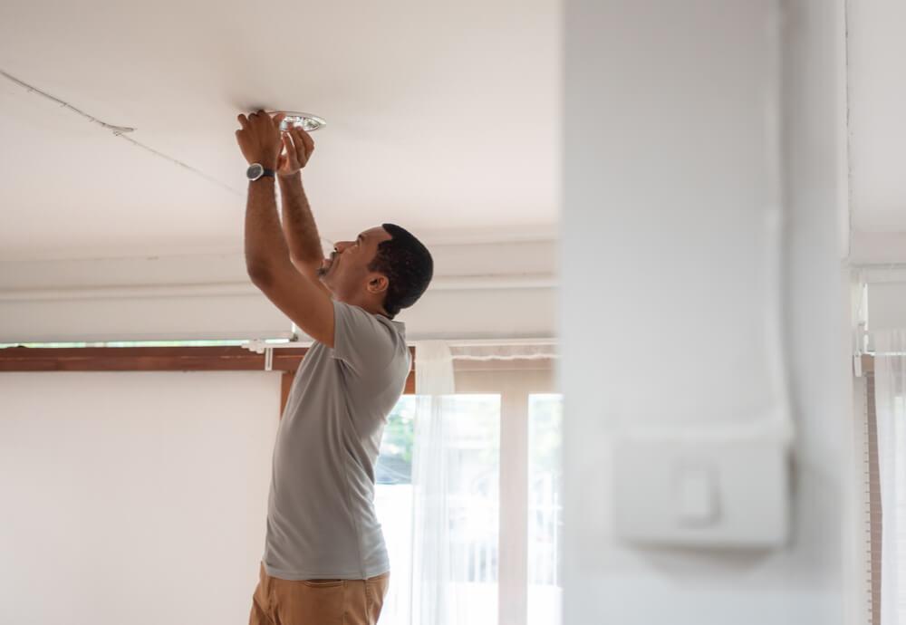 Man installing LED light at home