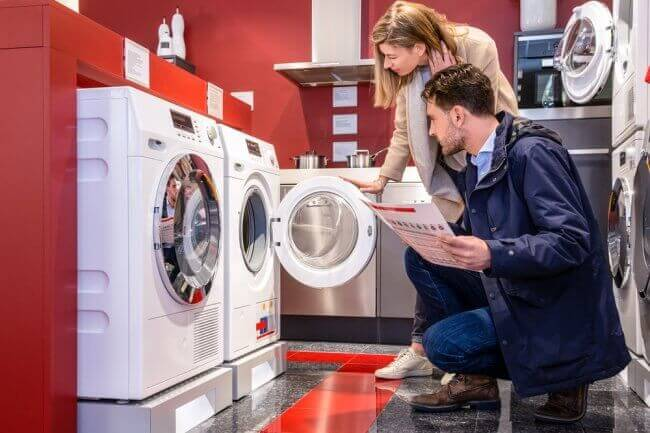 A couple looking at washing machines
