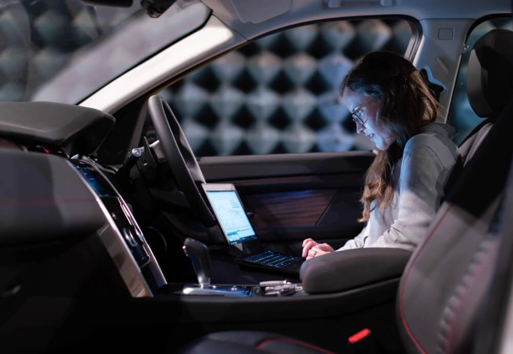 a woman working on a laptop while sitting in a car